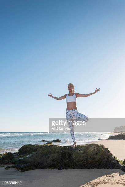 Frau steht mit ausgebreiteten Armen auf Felsen am Strand in Yogapose Baum