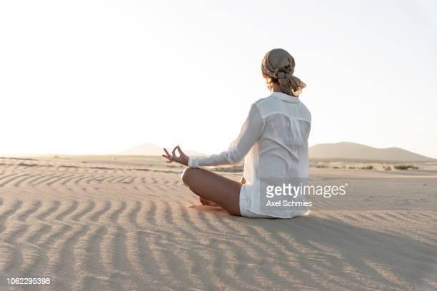 frau von hinten im meditationssitz auf sandigem boden mit wellenmuster - frau photos et images de collection