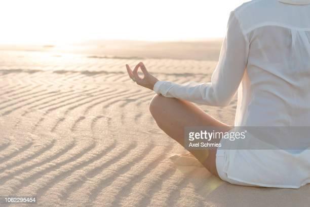 Frau von hinten im Meditationssitz auf sandigem Boden mit Wellenmuster
