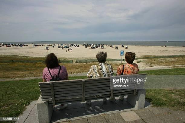 Frauen auf einer Bank am Strand von Neuharlingersiel Nordsee