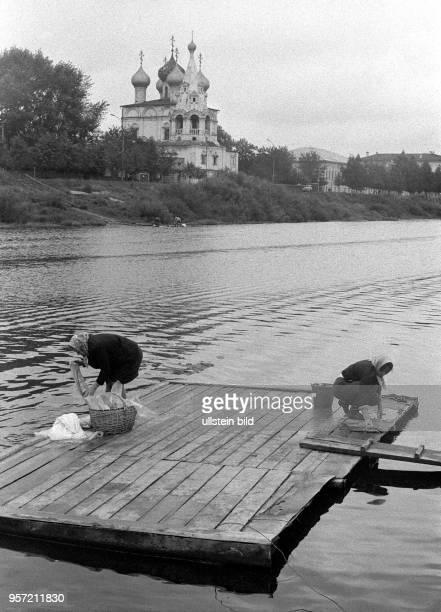 Frauen aus der Stadt Wologda waschen im Wasser eines Flusses ihre Wäsche, im HIntergrund die Sophienkathedrale am Kreml von Wologda, aufgenommen...
