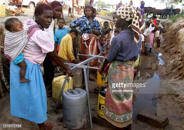 Frauen und Kinder füllen am 1032000 im Flüchtlingslager von Chiaquelane an einer Wasserausgabestelle ihre Kanister Trinkwasser ist für die...