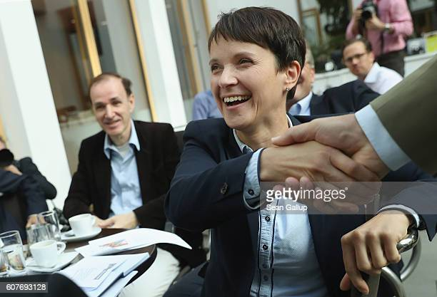 Frauke Petry cohead of the Alternative fuer Deutschland political party greets a colleague while sitting with other leading AfD party mebers prior to...