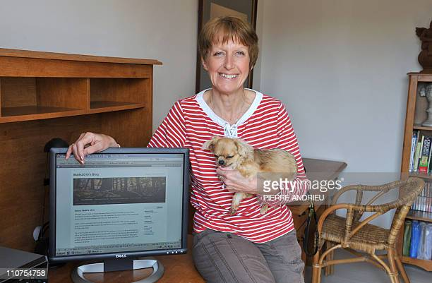 FRAYSSEBritish MariaLouise Sawyer poses with her dog next to her computer on March 16 2011 at her home in the French western village of Chazelles...