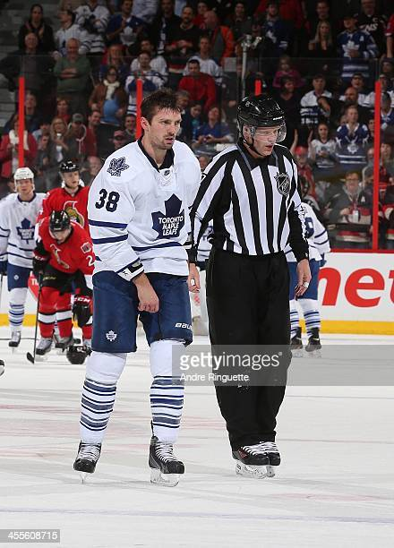 Frazer McLaren of the Toronto Maple Leafs is escorted off the ice by a linesman in a game against the Ottawa Senators at Canadian Tire Centre on...