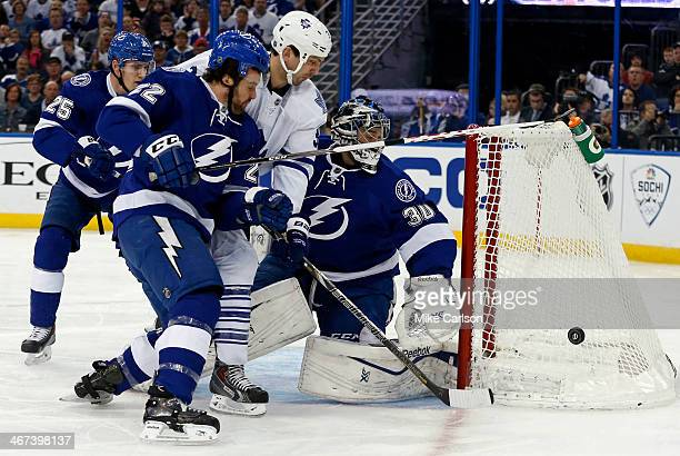 Frazer McLaren of the Toronto Maple Leafs is sandwiched between goalie Ben Bishop and defender JeanPhilippe Cote of the Tampa Bay Lightning at the...