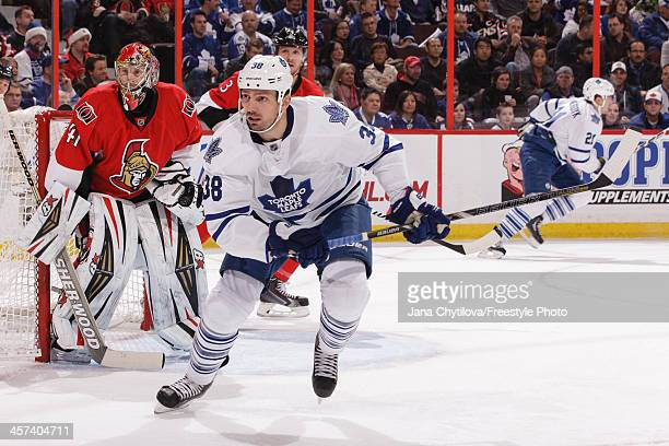 Frazer McLaren of the Toronto Maple Leafs skates as Craig Anderson of the Ottawa Senators looks on during an NHL game at Canadian Tire Centre on...