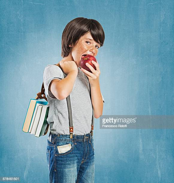 Freckled boy wearing braces, carrying bundle of books over shoulder, looking at camera, biting apple