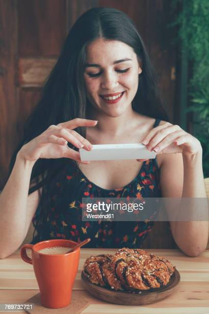 Freckled young woman taking picture of coffee and chocolate braids with smartphone