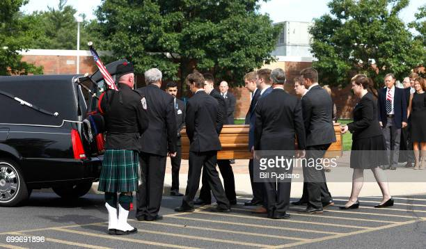 Fred and Cindy Warmbier watch as the casket of their son Otto Warmbier is carried out from his funeral at Wyoming High School June 22 2017 in Wyoming...