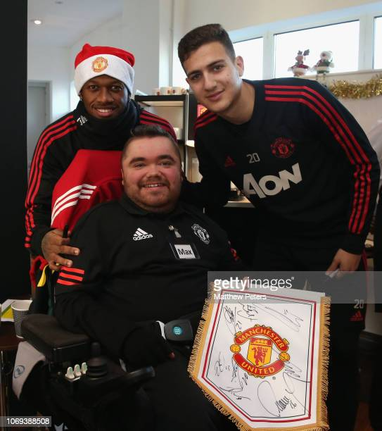 Fred and Diogo Dalot of Manchester United pose with Max during the MU Foundation's Dream Day for fans with lifelimiting illnesses at Aon Training...