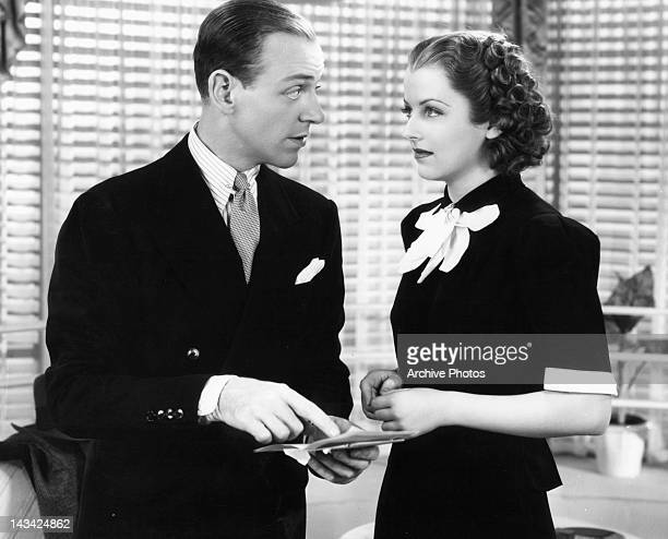 Fred Astaire and Betty Furness talking over note in a scene from the film 'Swing Time', 1936.
