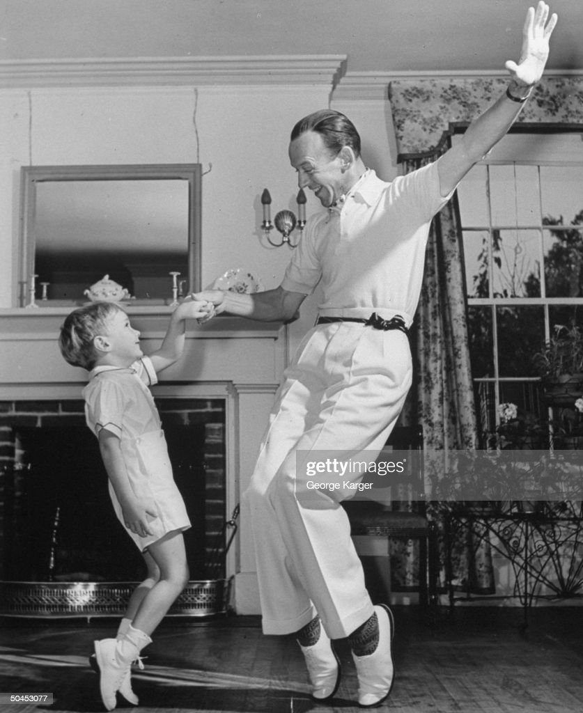 Fred Astaire dancing with his son in living room at home