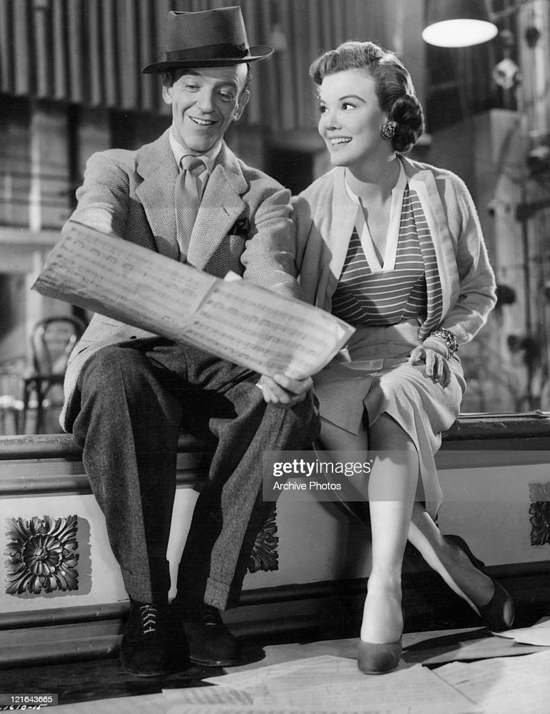 Fred Astaire is sitting next to Nanette Fabray reading music in a scene from the film 'The Band Wagon', 1953.