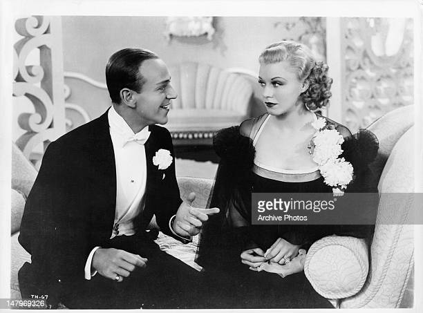 Fred Astaire talking to Ginger Rogers on couch in a scene from the film 'Top Hat' 1935