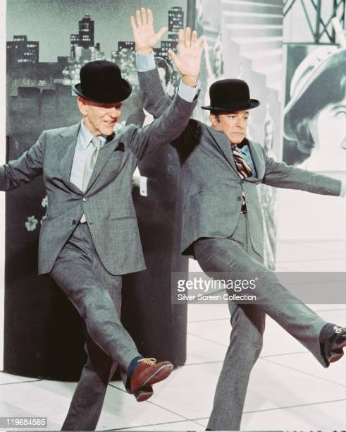 Fred Astaire US actor and dancer and Gene Kelly US actor and dancer both dancing and dressed in grey suits and bowler hats in a publicity still...