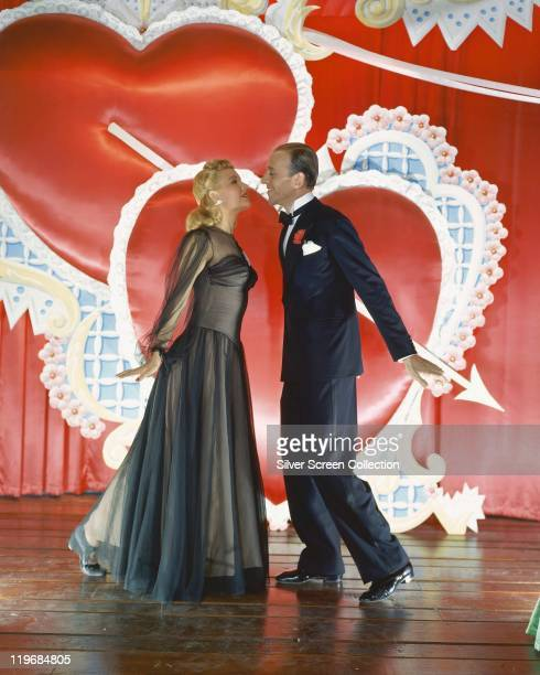 Fred Astaire US actor and dancer wearing a dark blue suit and bow tie and Marjorie Reynolds US actress and dancer wearing a black evening gown with...