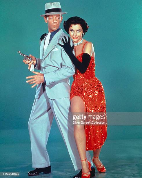 Fred Astaire US actor and dancer wearing a light blue suit and fedora with a black band and Cyd Charisse US actress and dancer wearing a red...