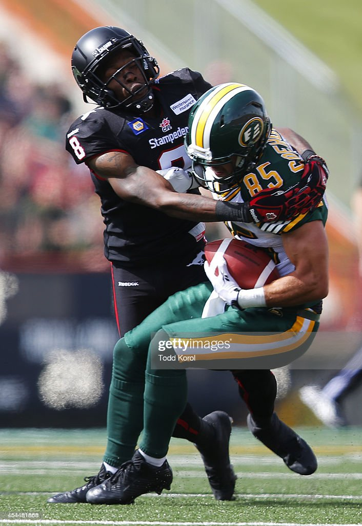 Fred Bennett #8 of the Calgary Stampeders tackles Nathan Coehoorn #85 of the Edmonton Eskimos in the first half of their CFL football game September 1, 2014 at McMahon Stadium in Calgary, Alberta, Canada.