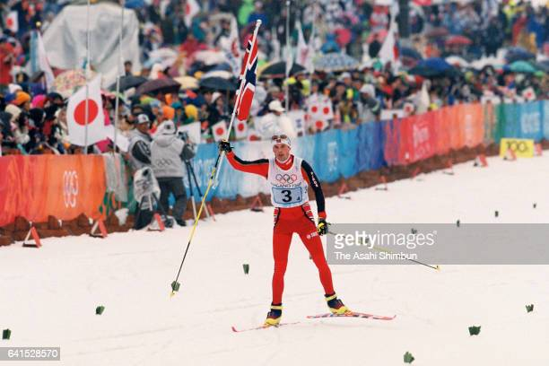 Fred Borre Lundberg of Norway holding the national flag approaches to the finish line to win the gold medal in the Nordic Combined Team during day...