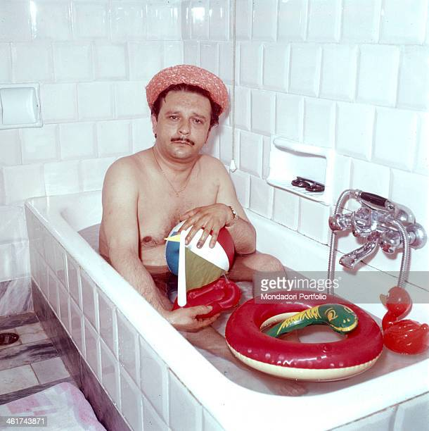 Fred Buscaglione born Ferdinando Buscaglione Italian songwriter and actor is bathing in a bath tub he is holding in his hands a colored plastic ball...
