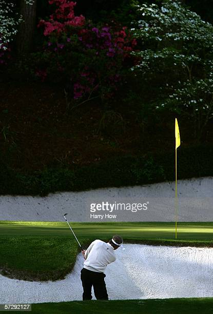 Fred Couples chips out of the bunker on the 12th green during the continuation of the rain delayed third round of The Masters at the Augusta National...