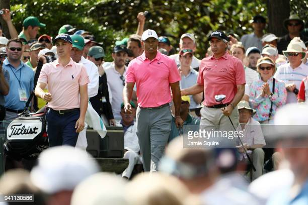 Fred Couples Justin Thomas and Tiger Woods of the United States walk off the seventh tee during a practice round prior to the start of the 2018...