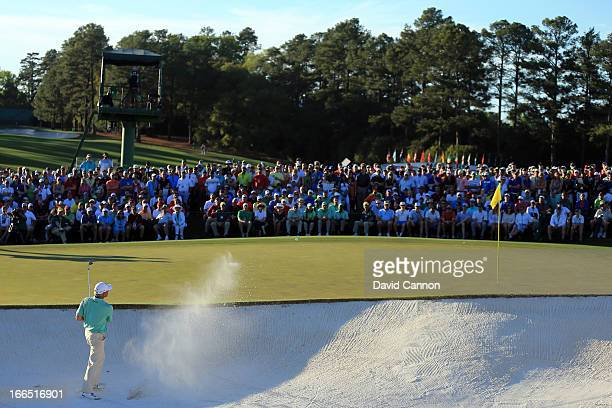 Fred Couples of the United States hits out of a bunker on the 18th hole the third round of the 2013 Masters Tournament at Augusta National Golf Club...