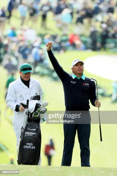 Fred Couples of the United States reacts on the first fairway alongside caddie Mark Chaney during the first round of the 2017 Masters Tournament at...