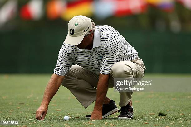 Fred Couples picks up some loose impediments on the first hole during the first round of the 2010 Masters Tournament at Augusta National Golf Club on...