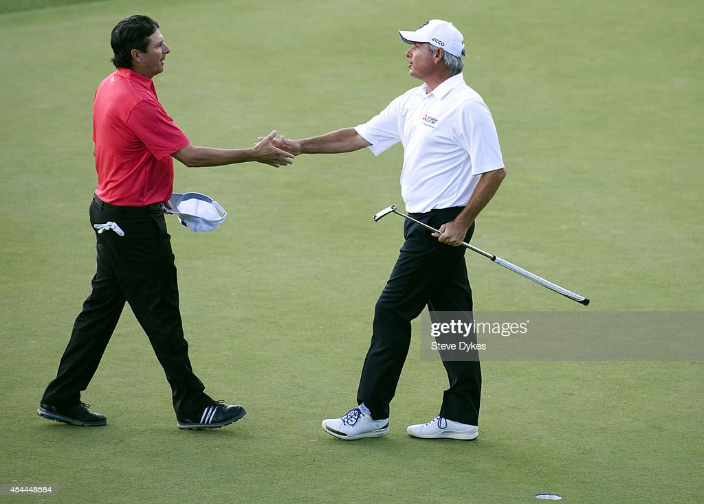 Fred Couples shakes hands with with Billy Andrade after tapping in his birdie putt on the 18th green to win the playoff after the final round of the Shaw Charity Classic at the Canyon Meadows Golf & Country Club on August 31, 2014 in Calgary, Canada.