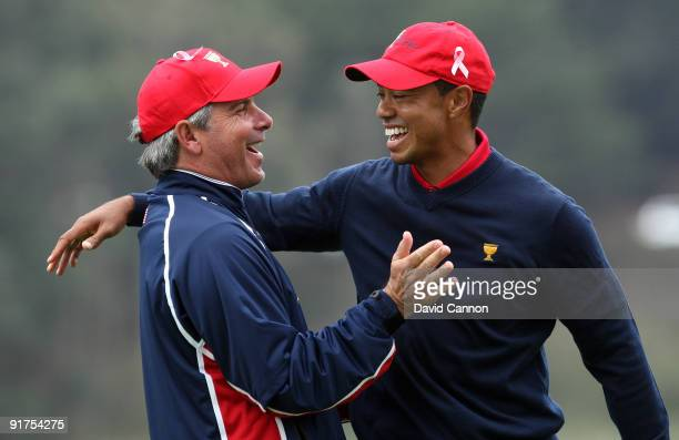 Fred Couples the Captain of the USA Team races to congratulate Tiger Woods after he had holed the winning putt at the 13th hole where he beat his...