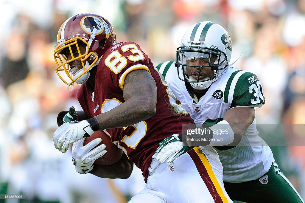 Fred Davis #83 of the Washington Redskins breaks a tackle by Donald Strickland #30 of the New York Jets at FedExField on December 4, 2011 in Landover, Maryland.
