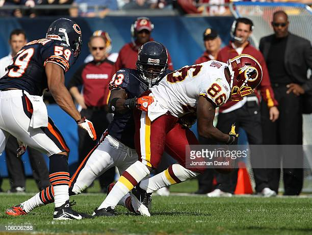 Fred Davis of the Washington Redskins fumbles the ball as he is hit by Charles Tillman of the Chicago Bears as Pisa Tinoisamoa closes in at Soldier...