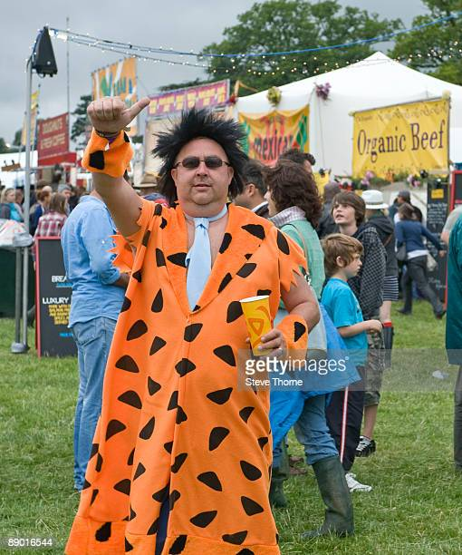 Fred Flintstone impersonator in the crowd on the first day of Cornbury Festival on July 11 2009 in Cornbury Park Charlbury Oxfordshire United Kingdom
