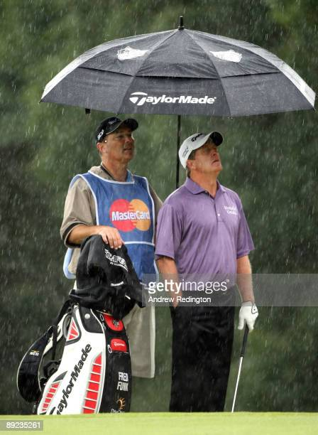 Fred Funk of the USA and his caddie wait in the rain on the ninth hole during the second round of The Senior Open Championship presented by...