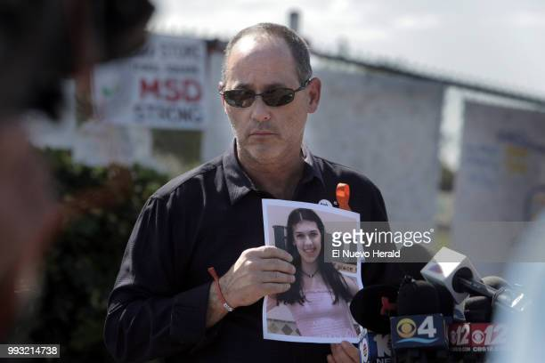 Fred Guttenberg holds a picture of his slain daughter Jaime as he listens to questions from the media in front Stoneman Douglas high school on March...