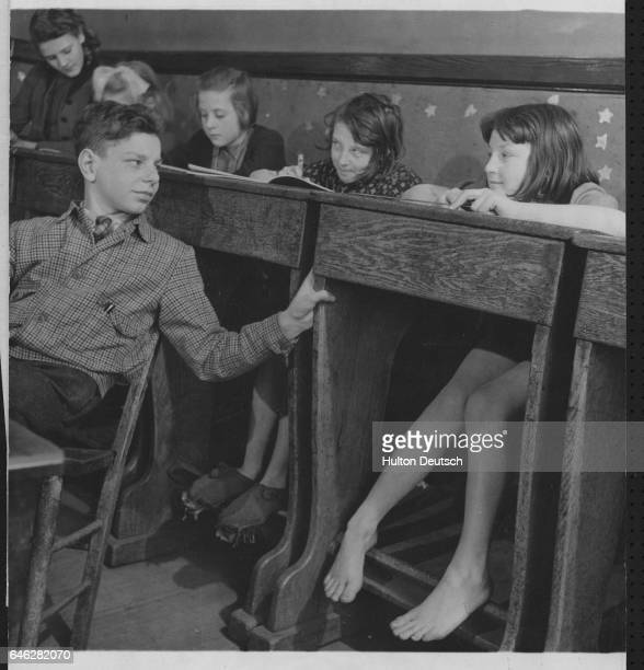 Fred Haslam turns round to speak to other students Norma Richardson with bare feet and Constance Wrigley in a lesson at a school in Prestolee The...