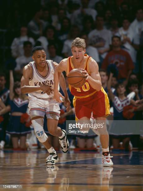 Fred Hoiberg, Guard for the Iowa State Cyclones dribbles the ball down court past Steve Woodberry of the University of Kansas Jayhawks during their...