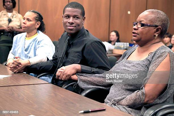 Fred Jingles holds the hand of his biological mother Kimberly Freeman and his adoptive mother LaVetta White in Pasadena Juvenile Court during his...