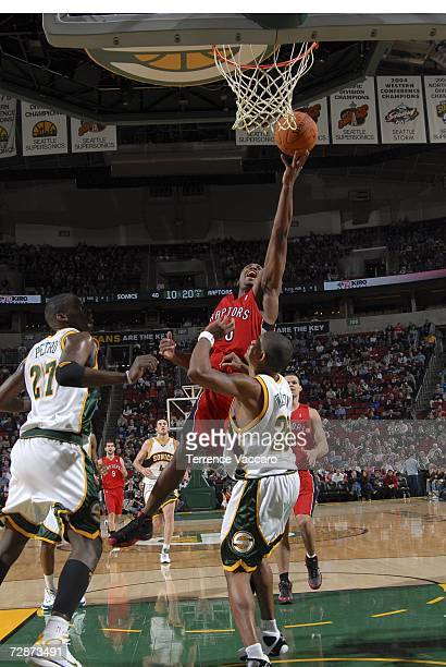 Fred Jones of the Toronto Raptors goes to the basket against Earl Watson and Johan Petro of the Seattle SuperSonics at the Key Arena December 23 2006...