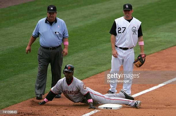 Fred Lewis of the San Francisco Giants slides safely into third with an RBI triple in the fifth inning as Garrett Atkins of the Colorado Rockies and...