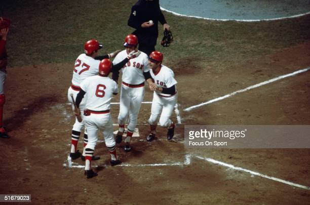 Fred Lynn of the Boston Red Sox crosses home plate after hitting a first inning home run as teammates Carl Yastrzemski Carlton Fisk and ondeck batter...