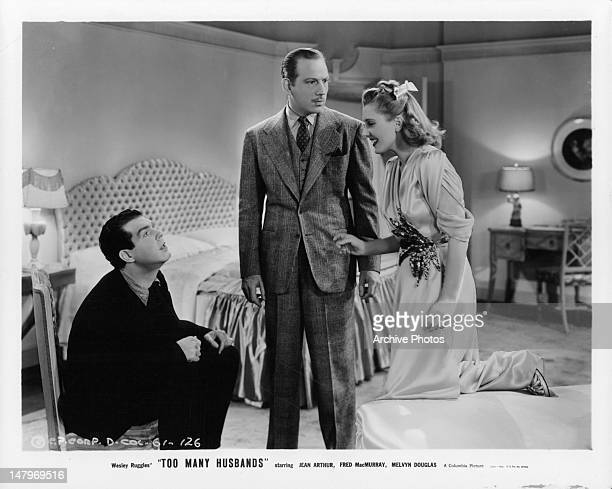 Fred MacMurray and Melvyn Douglas listening to Jean Arthur in a scene from the film 'Too Many Husbands' 1940