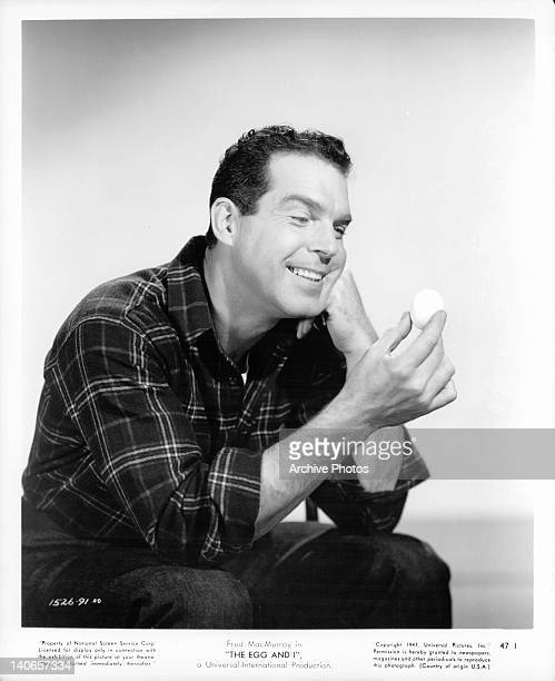 Fred MacMurray sitting starring at an egg in a scene from the film 'The Egg And I' 1947
