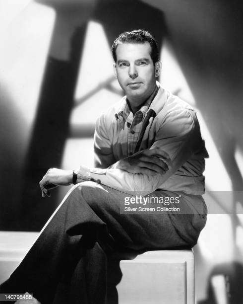 Fred MacMurray US actor sitting on a pedestal with his legs crossed in a studio portrait against background of shadows circa 1950