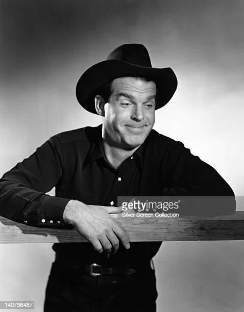 Fred MacMurray US actor with a moustache leaning on a fence and wearing a black shirt with a black cowboy hat circa 1950