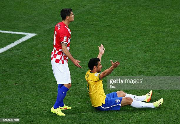 Fred of Brazil gestures for a foul from the ground as Dejan Lovren of Croatia looks on in the second half during the 2014 FIFA World Cup Brazil Group...