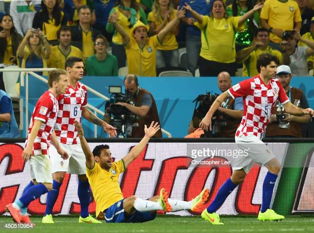 Fred of Brazil sits on the field gesturing for a foul against Dejan Lovren of Croatia during the 2014 FIFA World Cup Brazil Group A match between...
