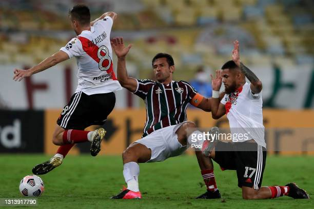 Fred of Fluminense competes for the ball with Agustín Palavecino and Paulo Díaz of River Plate during a match between Fluminense and River Plate as...